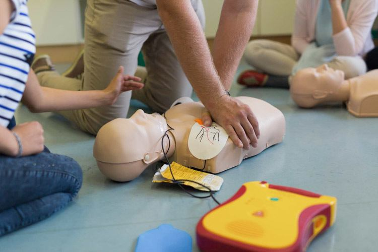 A Group of candidates learning to use a defibrillator during a first aid course