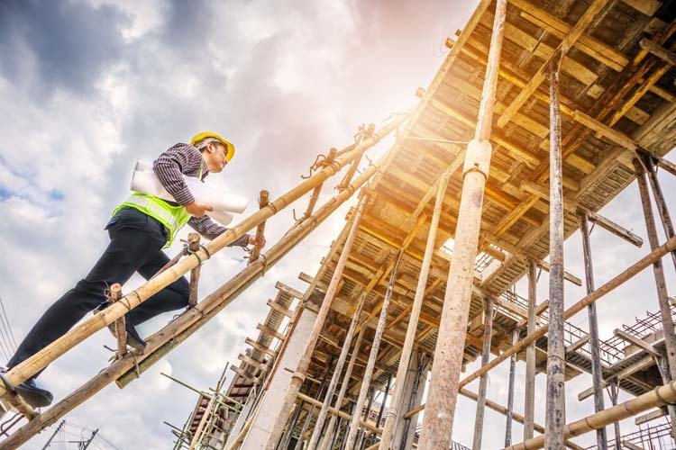 Construction worker climbing scaffolding on construction site