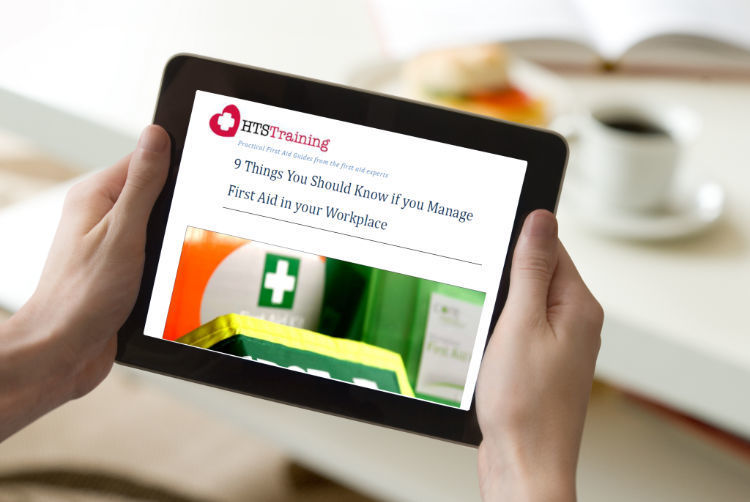 Person holding ipad and reading 9 Things you should know if you manage first aid ebook