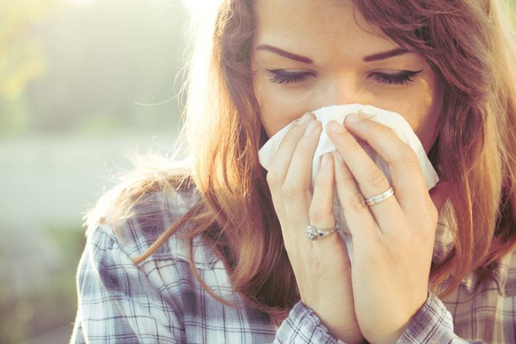 Woman suffering from hayfever causing sneezing