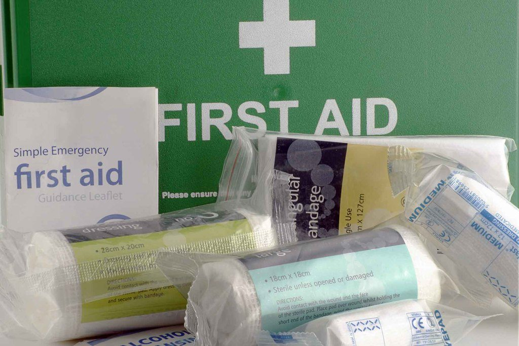 Green first aid box showing selected kit contents