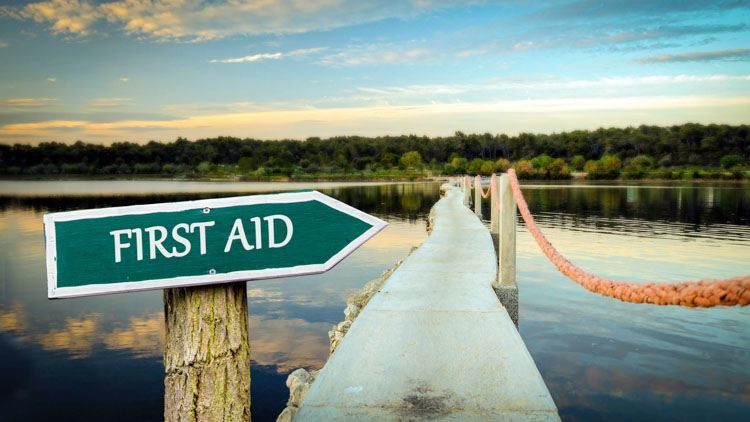 First Aid sign pointing across a calm lake