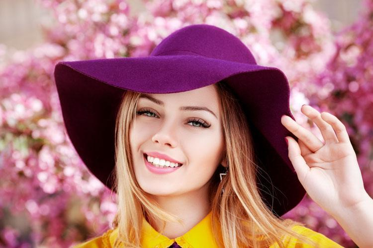 Woman wearing purple hat in front of flowery purple background